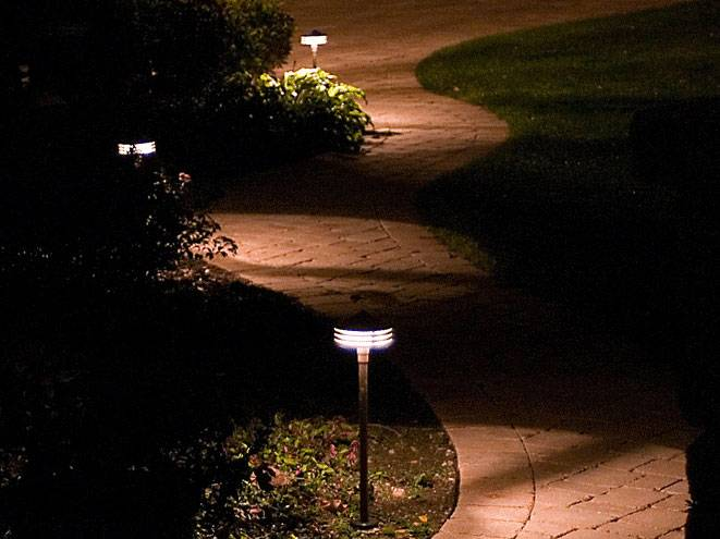 Outdoor lighting fixtures on a stone pathway.