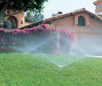 Lawn sprinklers in action in front of a house.