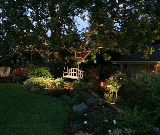 Garden swing with landscape lighting in addition to professional patio lighting.