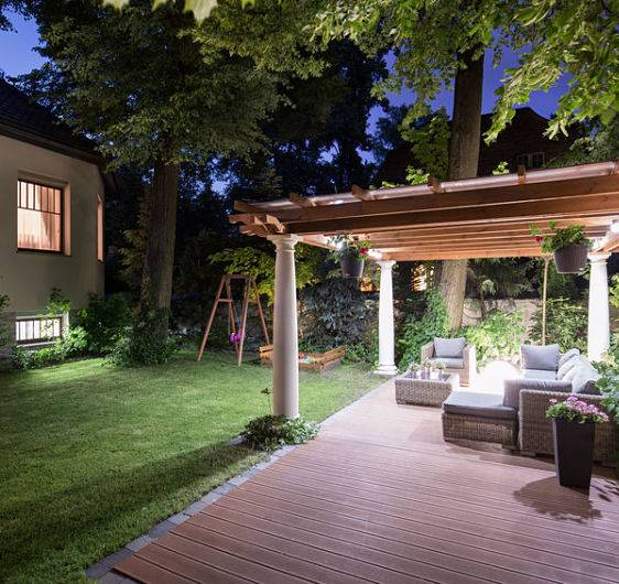 A backyard with a covered patio and a patio lighting system done by American National Sprinkler & Lighting.