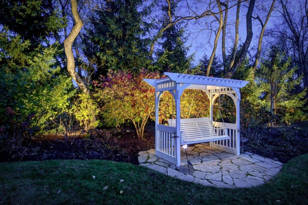 American National Sprinkler & Lighting - automatic lighting system illuminating a white bench in the backyard.